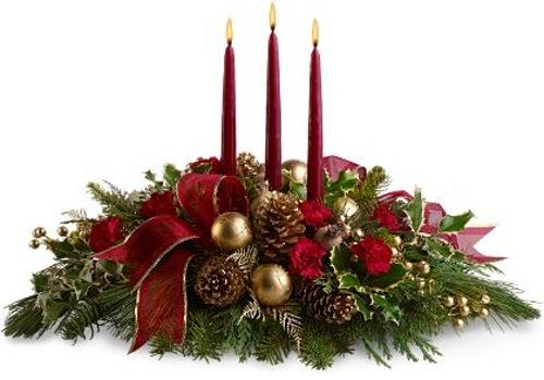 en este centro de mesa predomina el verde de las ramas de pino acompaando con tres velas rojas en el centro algunos flores del mismo color y pias